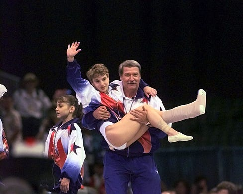 Bela Karolyi holds Kerri Strug after the USA team won the gold medal Tuesday in team gymnastics finals in Atlanta. Strug injured her leg on a vault when she landed short, but bravely came through on her second. Karolyi carried Strug to the medal ceremony creating one of the most iconic images in sports.