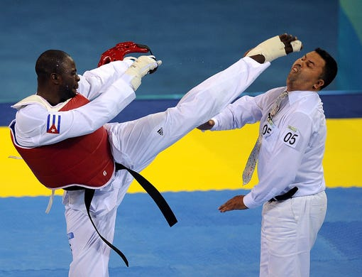 Angel Valodia Matos of Cuba lands a kick to the head of referee Chakir Chelbat of Sweden after being disqualified from his bronze medal contest in the men's +80 kg taekwondo competition against Arman Chilmanov of Kazakhstan during the 2008 Beijing Olympic Games in Beijing.