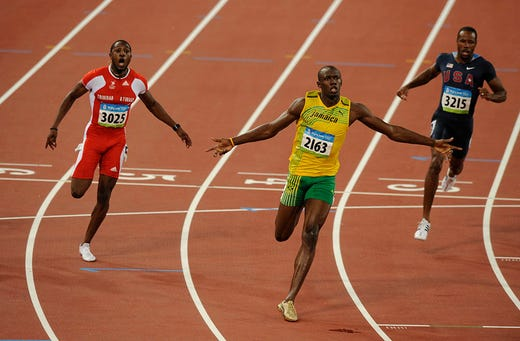 Gold medalist Usain Bolt, center, of Jamaica crosses the finish line in new world record time of 9.69 seconds ahead of silver medalist Richard Thompson, left, of Trinidad/Tobago, and last place finisher USA's Darvis Patton, right, in the finals of the men's 100 meter run during the 2008 Beijing Olympics. One of the greatest sprinters of all time, Bolt won the 100 and 200 meters. He would do the same in 2012 and 2016 also helping Jamaica to win the 4x100 relay.