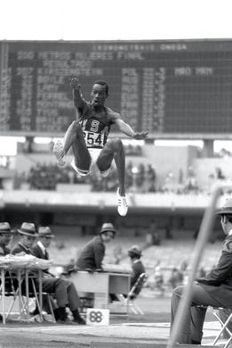 Bob Beamon of the USA breaks the Long Jump World Record during the 1968 Olympic Games in Mexico City. Beamon long jumped 29 ft 2 1/2 in, winning the gold medal and setting a new world record. It is the first jump over 28 ft. While the middle distance runners from the low level countries floundered in the thin air of Mexico City, those in the explosive events reached new peaks, none higher than Beamon, who added almost 23 inches to the world record with a jump.  In Imperial measure terms it looked even more impressive since he missed out 28 feet, taking the record to 29 ft 2 ins. It was twelve years before anyone else reached 28 feet and the record stood until 1991 when Mike Powell of the US leapt 29.3 feet in Tokyo to win the world title.