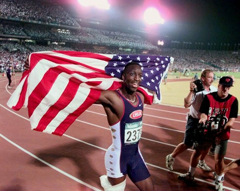 Michael Johnson carries the American flag while taking his victory lap after winning the 200 meter final, setting a world record at 19:32 at the Olympic Stadium in Atlanta. Johnson won the 200 and 400 at the same games, the only person to complete the double.