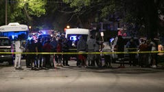Family members of the victims and neighbors gather at the scene of a fatal shooting, Monday, June 21, 2021, in the Greater Ville neighborhood in north St. Louis.