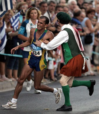 An unidentified man grabs Vanderlei Lima of Brazil during the Men's Marathon event at the 2004 Olympic Games in Athens. Lima was leading the race when the man pushed him off the course. He would eventually finish third.
