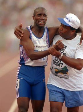 Derek Redmond of Great Britain winces in pain as he is helped by his father, Jim Redmond at the end of the men's 400 meter semi-final.  He was injured mid-way through the race, snapping his hamstring, but insisted on finishing. Redmond's father broke from stands and chased by officials, reached his son to help him cross the finish line, creating one of the most inspirational moments of all time.