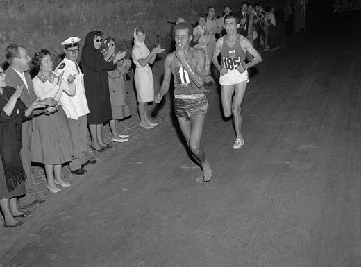 Ethiopian athlete Abebe Bikila runs barefoot for victory in the Rome 1960 Olympic Games marathon, after passing Moroccan Abdeslam Radi, on Sept. 10, 1960. One of the greatest marathon runners ever, Bikila would also win the 1964 Tokyo marathon, the first person to win consecutively,