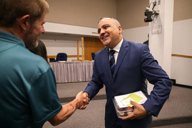 Incoming Round Rock school district Superintendent Hafedh Azaiez shakes hands with a parent at a board meeting this month. During its last regular meeting of thee school year, the school board approved a $467.4 million budget.