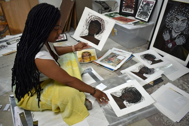 """Jamila Johnson sits amid her artwork in her Ames studio, looking at her """"Tignon"""" series of woodblock prints, which were inspired by headdresses worn by Black women."""
