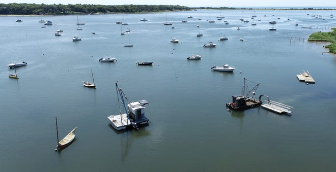 A quiet morning over Cotuit Bay as a work crew gets ready to move a dock section.