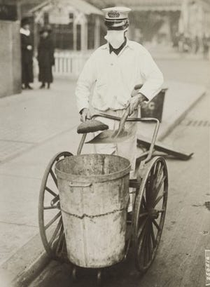 A street cleaner wears a face mask during the influenza pandemic of 1918. Image courtesy of the National Archives.