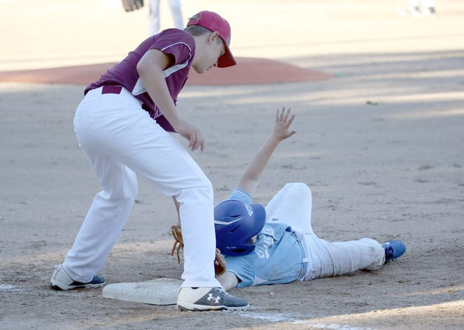 QuinlanAgency.com's Jaxson Stonecipher dives back to first in the second inning while Einspahr Construction first baseman Weston Rentel applies the tag in Cal Ripken Major Monday night at the COCOBA ballfield.