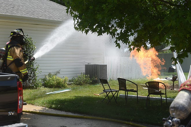 Columbia firefighters spray water to protect a house in the 4700 block of Sussex Drive on Wednesday while Ameren Corporation employees shut off a natural gas line to the house. A man struck the gas line while using a gas-powered earth auger to drill a hole. Two men received burns during the accident.