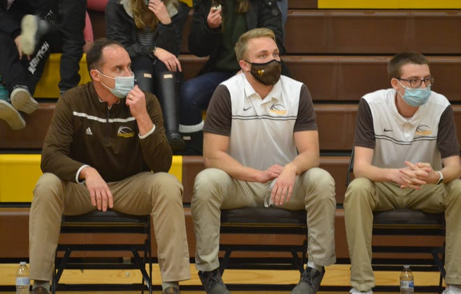 Pellston varsity boys basketball coach Larry Cassidy, far left, along with assistant coaches Nate Meinke and Jared Anderson, look on from the bench during a basketball matchup from this past season. Meinke, middle, has been hired as Pellston's new varsity boys head coach, replacing Cassidy, who guided the Hornets for the last eight seasons.
