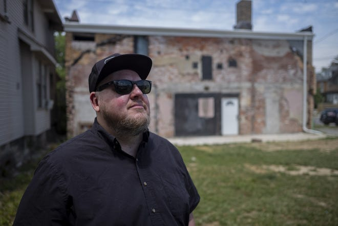 Local music promoter Bobby Miller in front of a vacant movie theater building at 367 Hudson St., where he and property owner Nick Wolak, who also owns Evolved Body Art nearby, hope to renovate the theater and convert it into a coffee shop by day and live music club at night.