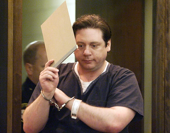 David L. Braden tries to hide his face with a folder as he enters a Franklin County Common Pleas courtroom for his sentencing on June 16, 1999.