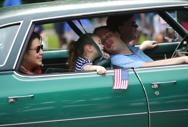 Participants enjoy the ride in a vintage Cadillac during the Upper Arlington Fourth of July parade in 2019.