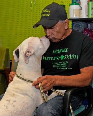 Ted Aranda gives a kiss to Daisy, a deaf 3-year-old dog, at the Lenawee County Humane Society.
