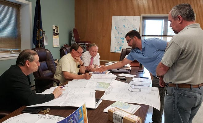 Co-Owner of Mountaintop Storage LLC Ryan Lupero directs Paupack Township Supervisor Jim Martin, Supervisor Bruce Chandler and Solicitor Ron Bugaj to areas on a map with Manager/Sr. Project Designer at Kiley Associates Lou Cozza at a hearing June 10, when discussing plans for construction at his company in Lakeville.  / Photo by Katie Collins