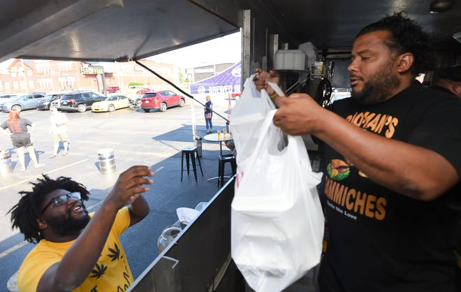 Lonnie Askia, left, from Erie, receives a food order from Chris Pacley of Bro-Man's Sammiches food truck outside Erie Ale Works in Erie.