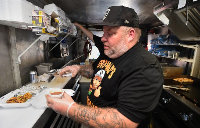 Stephen Stanbro, owner of Bro-Man's Sammiches food truck, serves customers outside Erie Ale Works, 412 W. 12th St.