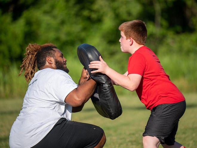 Fort Osage graduate Sima Thomas, a former All-America defensive lineman with Pittsburg State, works with a young participant in the Speed & Sport Youth Football Camp Tuesday at the Independence Athletic Complex. Thomas helped out at the camp run by his teammate on the 2015 Fort Osage state championship team, Elijah Penamon.
