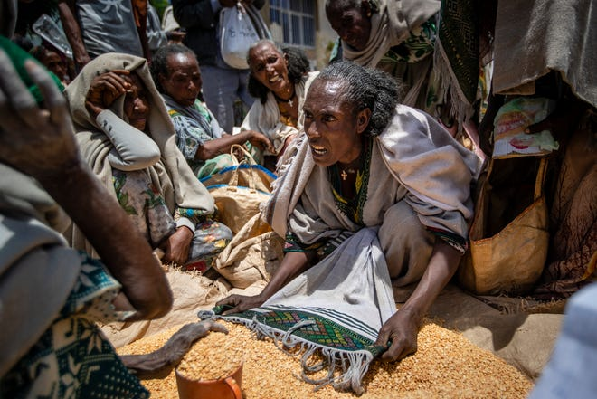 An Ethiopian woman argues with others over the allocation of yellow split peas after it was distributed by the Relief Society of Tigray in the town of Agula, in the Tigray region of northern Ethiopia, on Saturday, May 8, 2021. In war-torn Tigray, more than 350,000 people already face famine, according to the U.N. and other humanitarian groups.