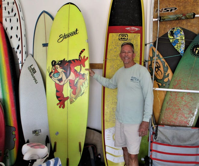 Barry Shaw is pictured with a collection of surfboards, including his son's custom-built Tony the Tiger surfboard. After learning to surf las a teen, Shaw had a successful banking career before competing in his first pro contest at 42.