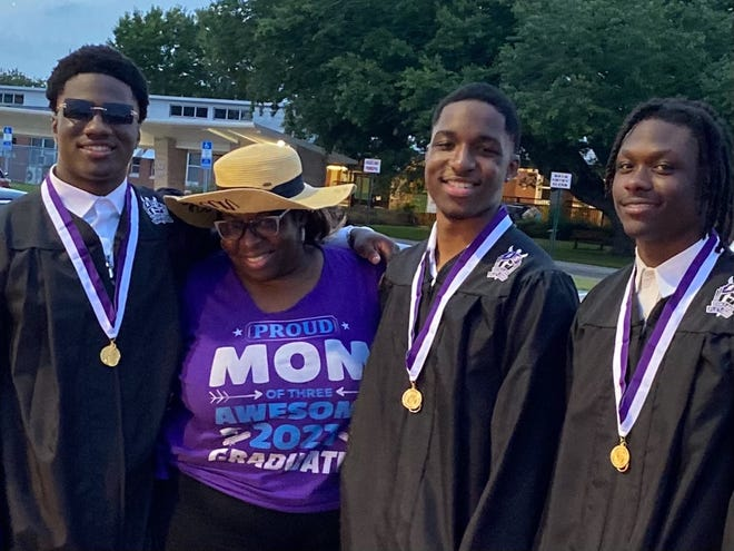 From left, triplets Joshua, Jeremiah and Jeffrey Davis with their mother, Elaine Haynes, as they celebrate the young men's graduation from Fletcher High School. The triplets have participated in activities and programs with the Beaches Boys & Girls Club since elementary school.