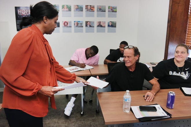 Nicole Kent, a career development instructor, hands out an activity for Ready4Work clients. The Operation New Hope program helps people emerging from the criminal justice system to re-enter the community and workforce.