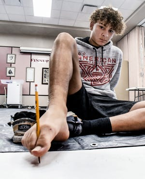 Dominic Mata, 14, holds a pencil between his toes to write his name on a strip of paper Tuesday during one of the events in a Silent Library game day for youth at the Finney County Public Library.