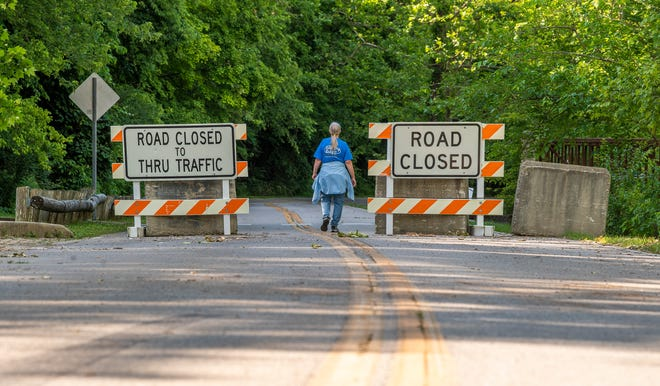 A woman walks by the road closed signs posted on North Old Ind. 37 Wednesday near Lower Cascades Park.