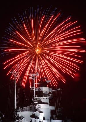 In this file photo, a fireworks burst explodes over the  Battleship Massachusetts radar tower at Battleship Cove in Fall River.