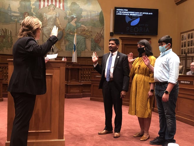 Peoria's new City Council member Kiran Velpula (middle) is sworn in by City Clerk Stephanie Tarr (left) Tuesday night at City Hall. Velpula was joined by his wife Swapna Ashvthkar and son Jai Velpula (right).