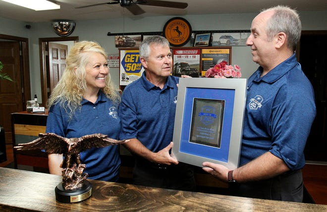 Nate Gustafson, right, hands a plaque to Dave Timm, center as Gina Timm stands next to a trophy given to Auto Repair Specialists from AAA naming the business Best in Auto Repair 2021 in the nation on Wednesday, June 23, 2021, in Freeport.