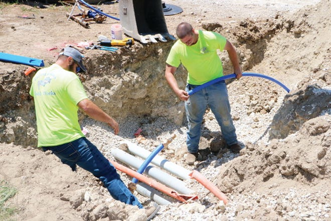 Public Works employee Lee Hunter (without hat) is shown installing a tap saddle on the 10-inch water main adjacent to Casey's.