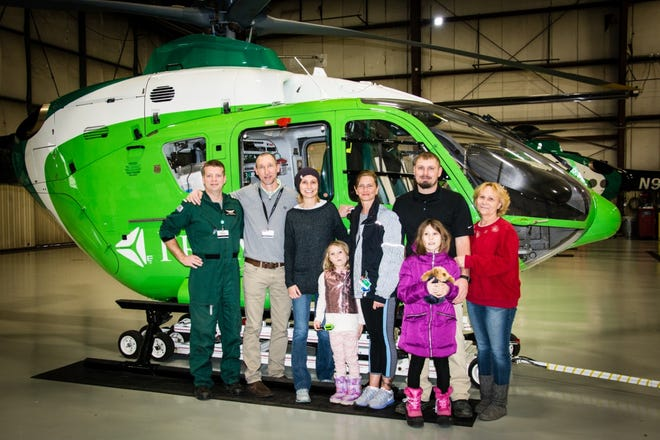 Brittany Markgraff (center, wearing a hat) stands with her family and the crew from ProMedica Lifeflight that transported her after her accident. From left: Pilot John; Paramedic Jeremy; Markgraff; Markgraff's daughter Madilyn; Nurse Paula; Markgraff's husband, Josh; Markgraff's daughter Makayla, and her mother, Lisa. Courtesy photos