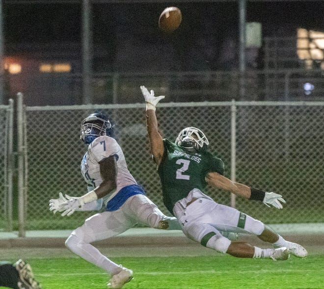 Sierra's Zion Bell makes a diving catch over Manteca's Trey Moreland during a varsity football game April 1 at Manteca's Guss Schmiedt Field.