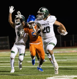 Manteca Buffaloes Blake Nichelson (20) runs the ball four yards during the third quarter in the game against Manteca High at Don Nicholson Stadium at Kimball High in Tracy on March 19.
