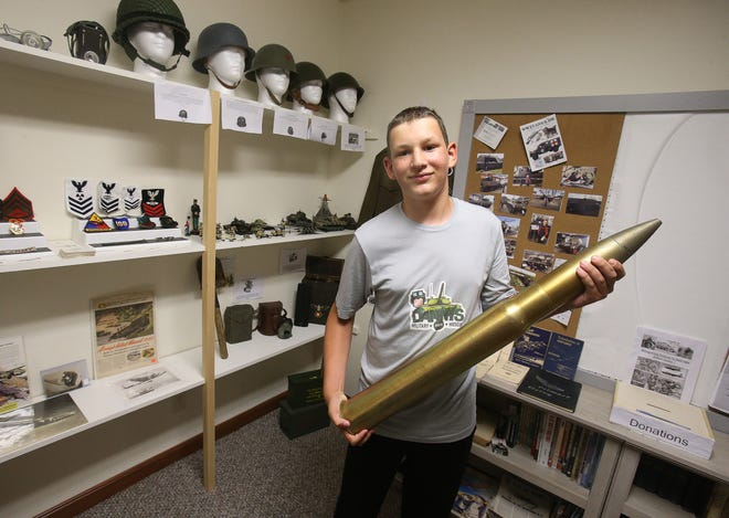 Thirteen-year-old Danny Gadzic shows off a 3-inch75mm naval round, part of his collection of military memorabilia that includes uniform patches, helmets, ammunition, training manuals and parts of military planes.