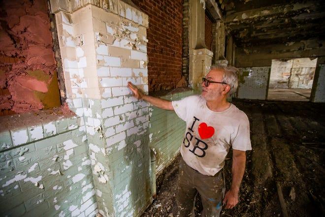 Mike Keen muestra los azulejos de cerámica el martes debajo de la pintura en el edificio Ward Baking Co. en South Bend.