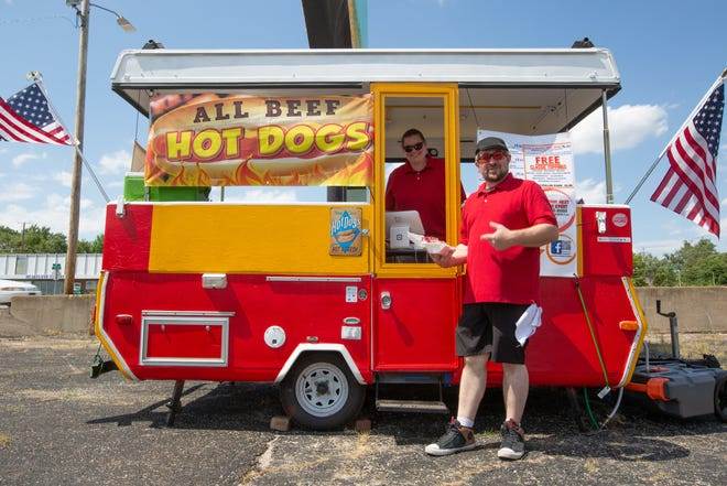 Dan Berthiaume and Jessica Brockstedt stand by their hot dog food truck Tuesday afternoon in the parking lot of Owls Nest Antique Mall & Flea Market, 2901 S.E. Adams St.