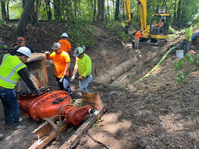 Crews with Dominion Construction Co. work to repair a water and sewer main near the Bryant Bridge over the Black Warrior River in Tuscaloosa, Ala.