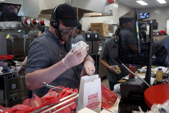 Store manager Seth Casto fills a customer's order during the June 22 grand opening of the new Sheetz convenience store and gas station at 9905 Johnstown Road in New Albany.