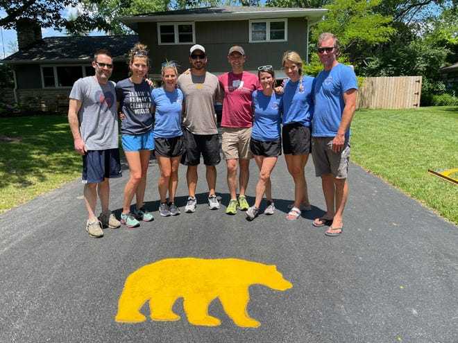 Upper Arlington Civic Association members (from left) George Pattison, Susie Pattison, Stacy McIntire, Brandon McIntire, Sam Porter, Sandi Porter, Michelle Gdovin and Steve Gdovin pose by one of the golden bears painted in the driveway of a resident.