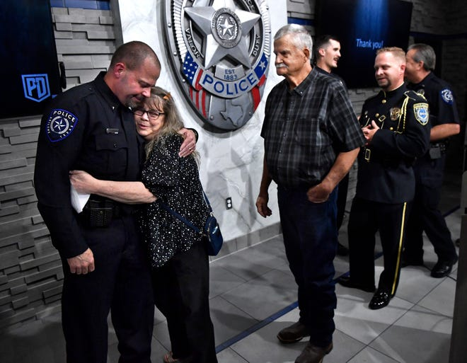 LaZeda Jordan hugs her son, Craig, her husband Tommy behind her, as Abilene Police Department officers line up to congratulate Craig who was promoted to assistant chief of Police on Wednesday. Chief Marcus Dudley promoted three others and honored Abilene citizens who assisted the community during the record February snowstorm.