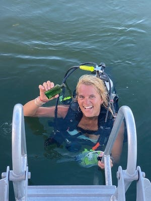 Jennifer Dowker, owner and founder of Nautical North Family Adventures found a 95-year-old message in a bottle while diving in the Cheboygan River on June 18, 2021.