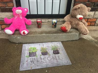 A memorial of teddy bears and candles adorns the doorstep of a Detroit home in the 18000 block of Northlawn in Detroit on Wednesday, June 23, 2021 where a man and woman were killed and their baby left alone inside for hours on Monday.