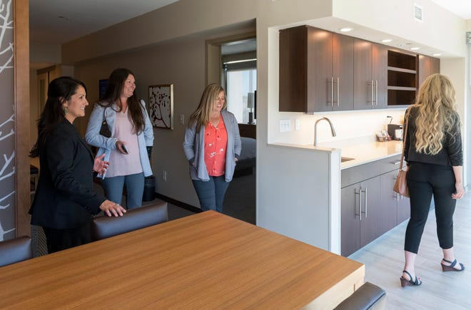 Director of Sales for Hyatt Place Evansville Janet Alexander, left, guides the sales staff from Visit Evansville through a corner suite during a grand opening celebration for the new hotel in Downtown Evansville Wednesday afternoon, June 23, 2021.