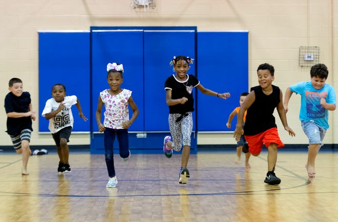 Kids race each other in the gym during the JFK Center Summer Youth Program in Henderson, Ky., Tuesday afternoon, June 22, 2021.