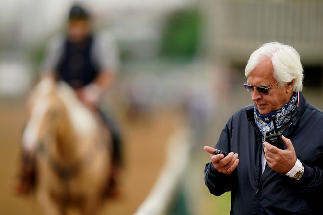 Trainer Bob Baffert checks his stopwatch while watching workouts at Churchill Downs Wednesday, April 28, 2021, in Louisville, Ky. The 147th running of the Kentucky Derby is scheduled for Saturday, May 1. (AP Photo/Charlie Riedel)