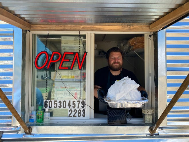 Bryant Bain serves an order at his new food truck Bain's Barbecue.